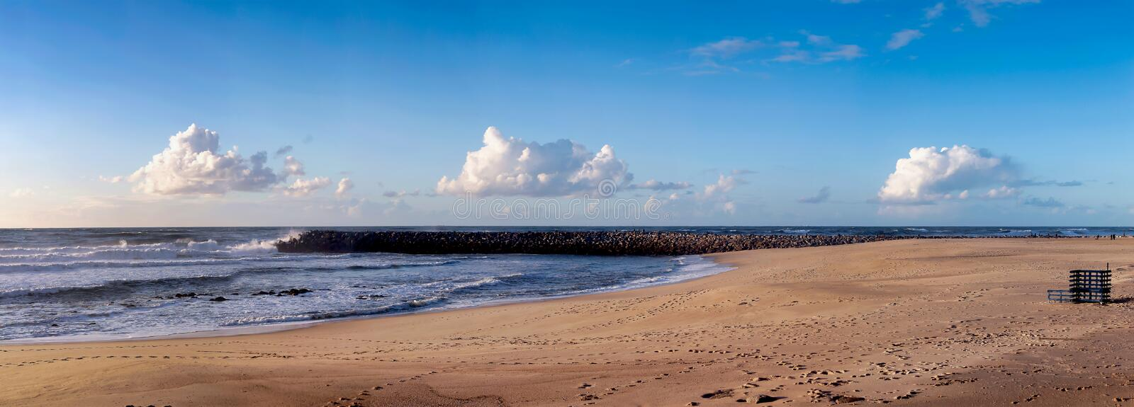 Large empty beach at daylight under a sunny blue cloudy sky stock image