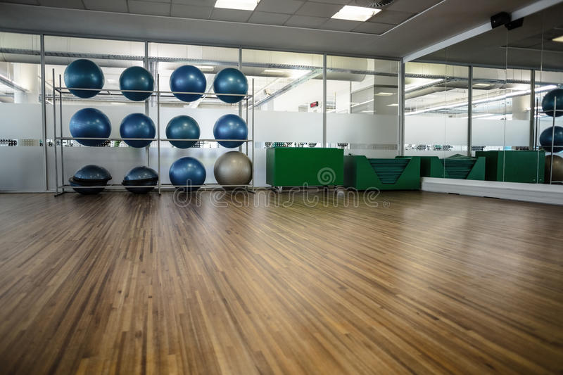 Large empty fitness studio with shelf of exercise balls royalty free stock photo