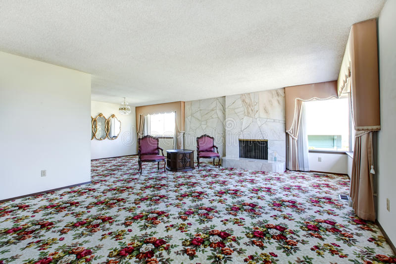 Large Empty Living Room With Floral Patterned Carpet Fire Place