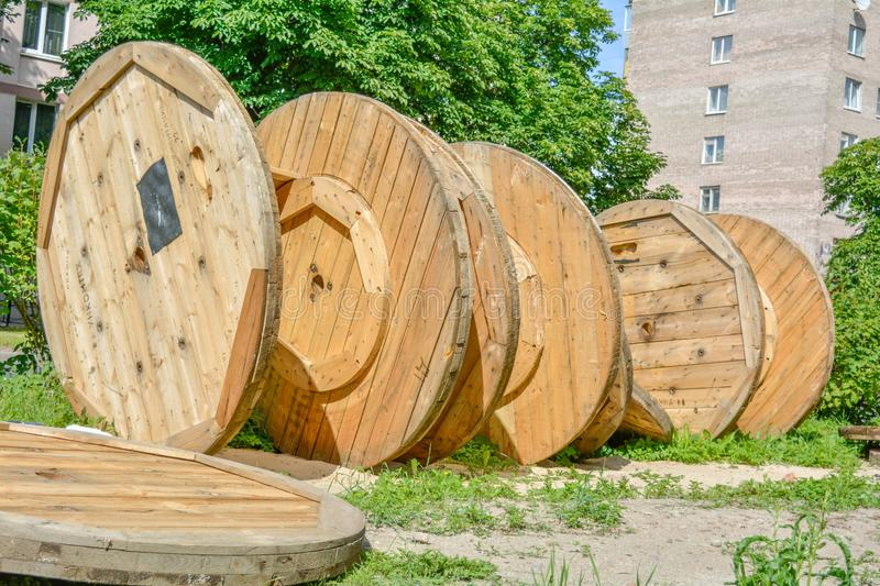 Large empty spools and reels of wooden cable drums stacked outdoor near houses stock images