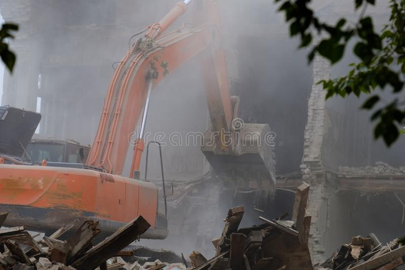 A large excavator breaks down the house, demolishing the house in the city, a lot of dust in the foreground branches. And debris from the building royalty free stock images