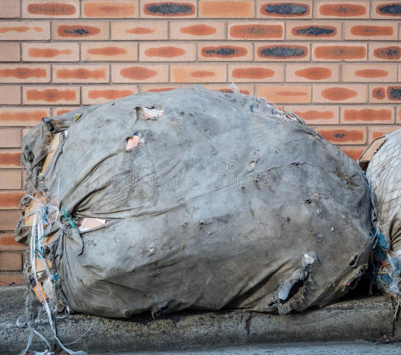 Large fabric bag of garbage or recycling on the side of road near brick wall stock images