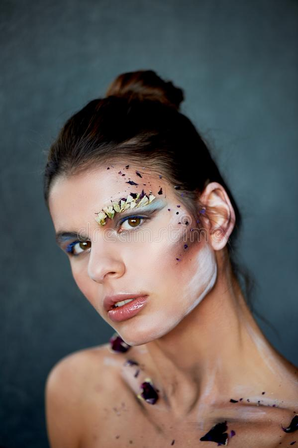 Large-face portrait. Smears on her face. The make-up using dry colors.Creative personality, model. royalty free stock photos