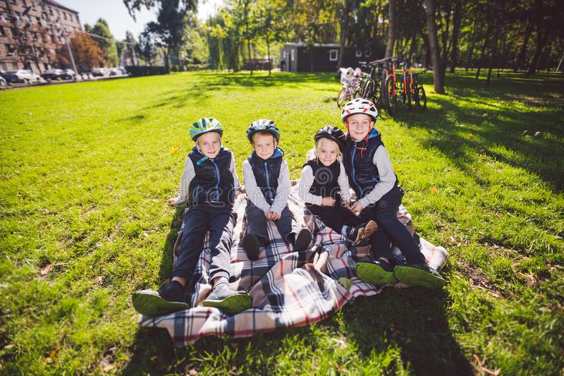 Large family Caucasian children. Three brothers and sister sitting resting on blanket outside the park. Green lawn grass. Background of bicycles. Funny kids in stock images