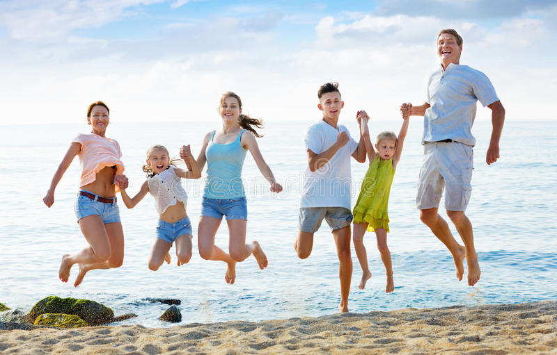 Large family jumping up together on beach on clear summer day royalty free stock photography