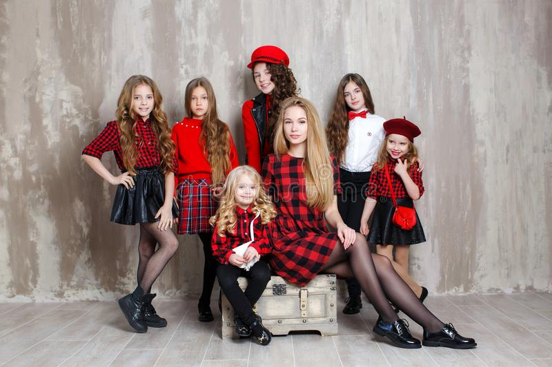 Seven pretty girls of different ages, six sisters are posing indoors during repairs. The large family.Seven pretty girls of different ages,seven sisters are royalty free stock images