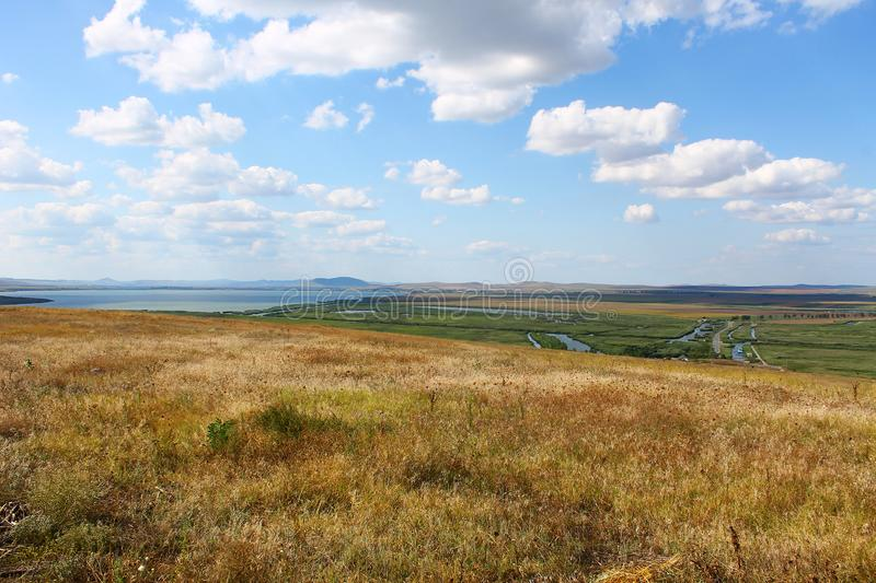 Large field near delta with clouds on blue sky. This nice field was captured near Danube Delta from Romania stock photo