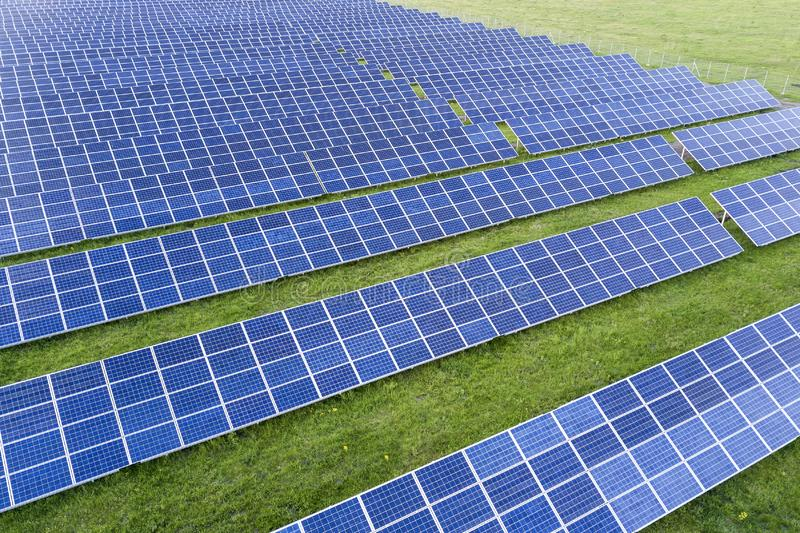Large field of solar photo voltaic panels system producing renewable clean energy on green grass background.  stock image