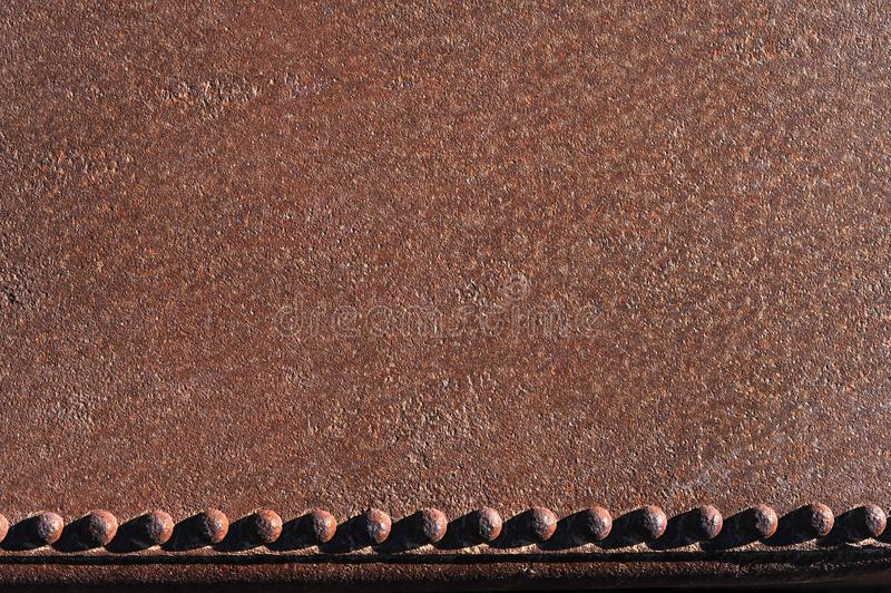 Large flat area of rusted iron with a row of old rusted rivets in a line at the base; abstract with rough impact stock images