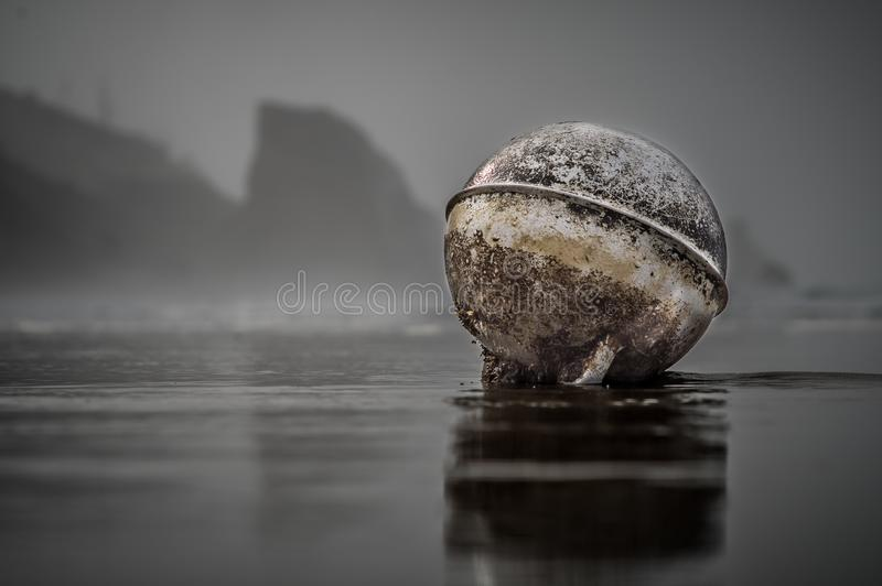 Float washed up on beach in front of cliffs. Large Float washed up on beach in front of cliffs on Oregon Coast stock photography