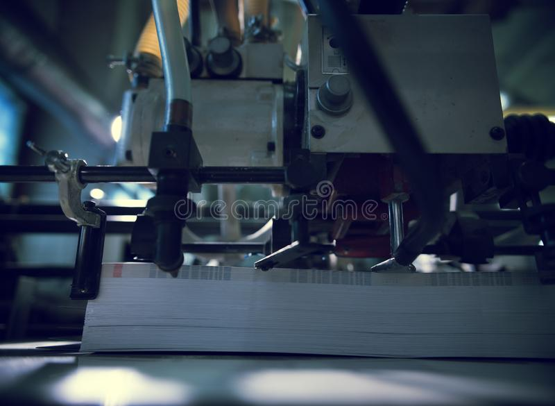 Large format printer with a pile of paper. Industrial printer machine with pile of paper newspapers, tabloids, print plant factory lying on conveyor after royalty free stock photography