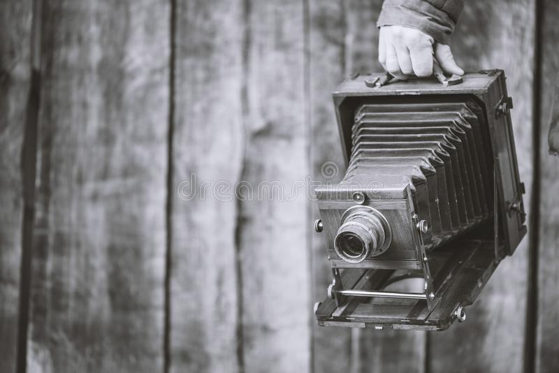 Large format retro camera, 5x7 inches. Photographer holds old studio camera. Monochrome effect, copy space. Concept - photography. Large format retro camera, 5x7 royalty free stock photos