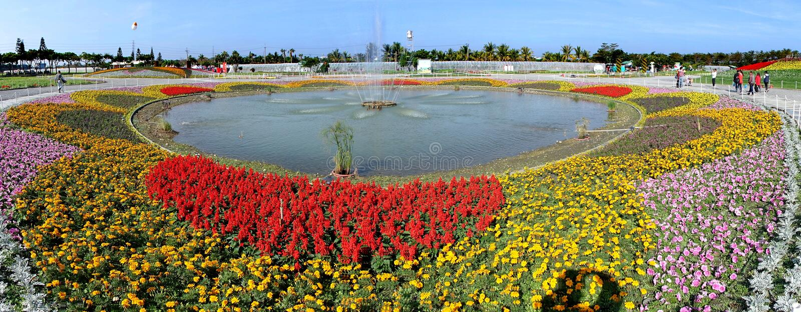 Large Fountain Surrounded by Flower Beds. PINGTUNG, TAIWAN -- FEBRUARY 14, 2018: A large fountain surrounded by colorful flower beds greets visitors at the royalty free stock photography