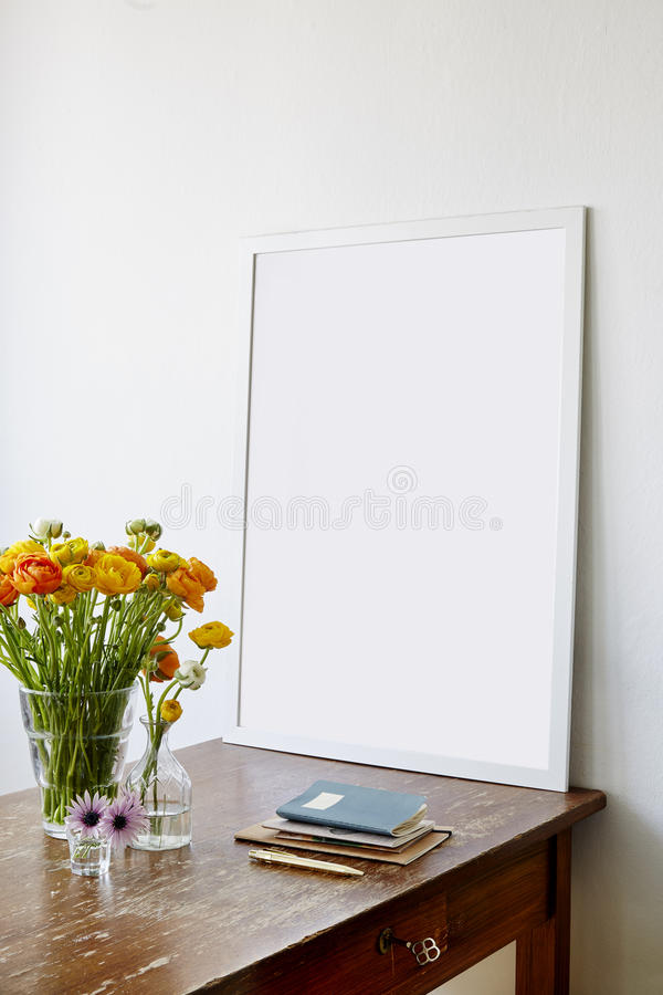 Large frame on vintage kitchen table and colorful flowers royalty free stock photography