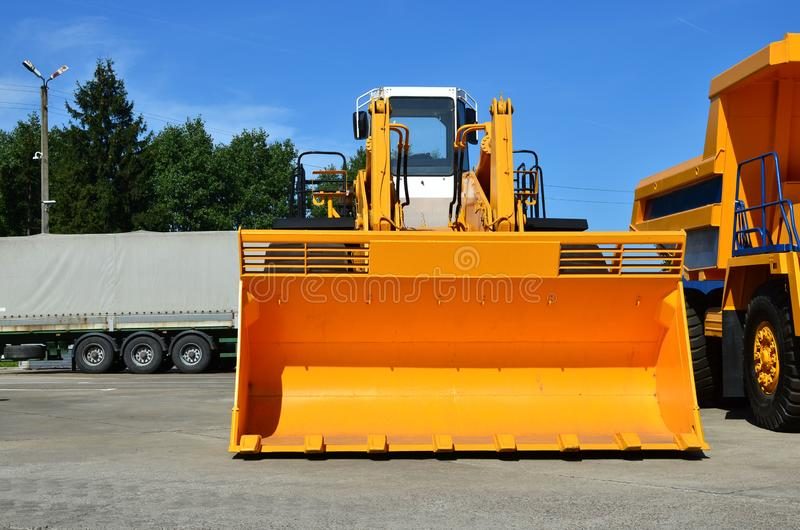 Large front-end loader or all-wheel bulldozer manufacture by the heavy vehicle plant. New heavy quarry equipment with bucket for sales. Coal mining, granite stock images