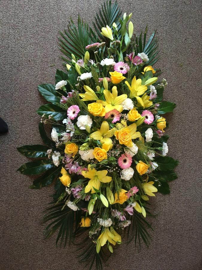 Large funeral spray. Funeral spray in yellow pink and white with lilies grebes royalty free stock photo