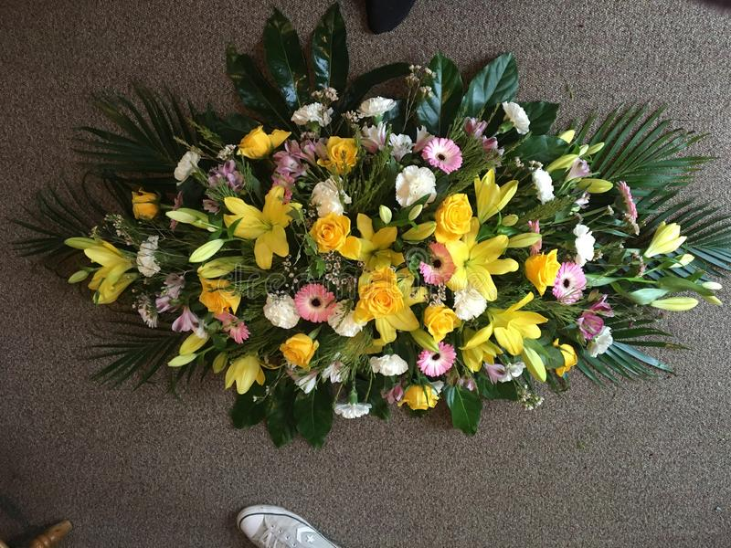 Large funeral spray. Funeral spray in yellow pink and white with lilies grebes royalty free stock image