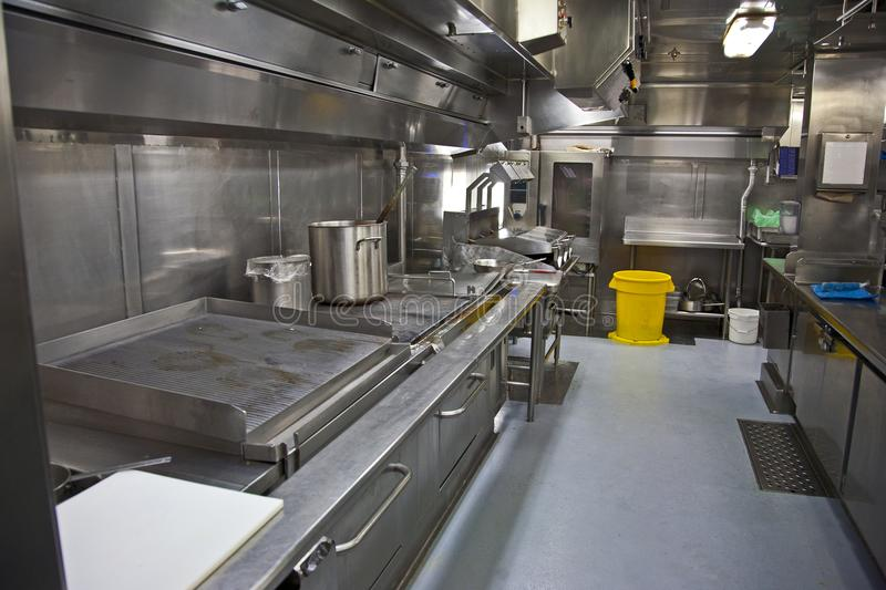 A large galley kitchen. Stainless steel surfaces and grills in an industrial sized kitchen stock photography