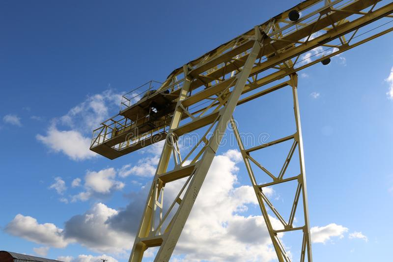 A large gantry crane. Made of metal colored yellow in the background of a bright blue sky with clouds close-ups moves the cargo stock photo