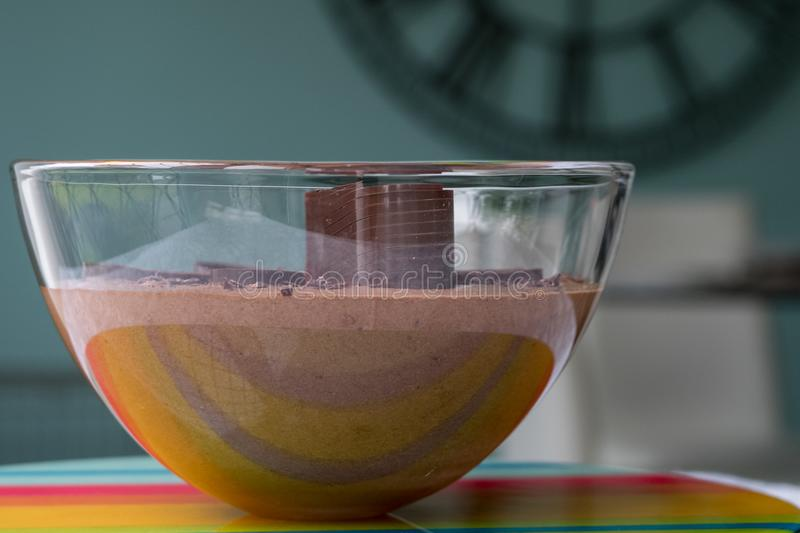 Large glass bowl of chocolate mousse standing on colourful glass platter, decorated with chocolate shavings and curls. stock images