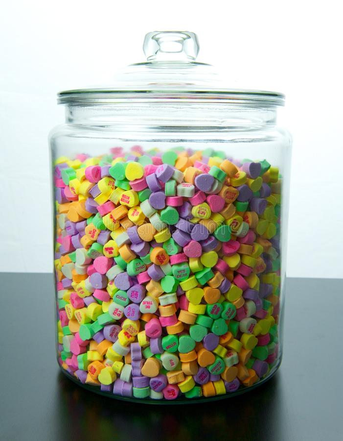 Large Glass Jar of Candy Hearts. Large glass jar of colorful candy hearts with lid sits on a black table with a white background royalty free stock photo