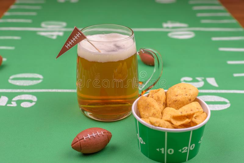 Large glass mug of cold beer on table with superbowl party decor. Game day beer and snacks on table decorated for the superbowl royalty free stock images
