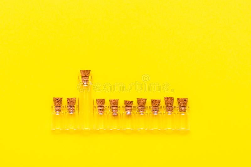 A large glass transparent empty bottle with corks in a row with the same small ones on a yellow background royalty free stock photo
