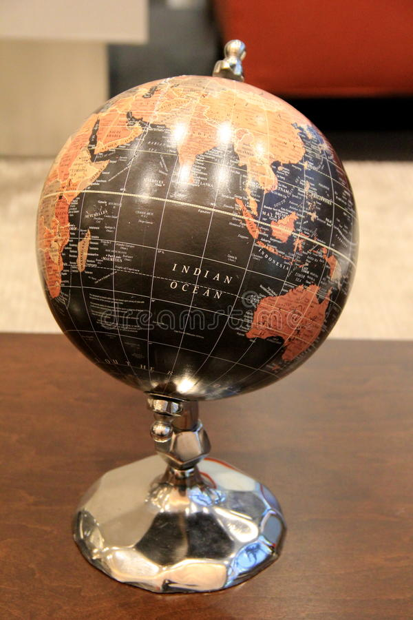 Large globe on spinner, set on wood table. Large globe of world on spinner, set as centerpiece on wood table, invites people to spin and find the next place they stock images