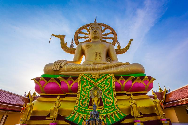 Large gold buddha statue in a sitting position under the blue sky at Big Buddha Temple is a famous tourist destination of Koh stock photography