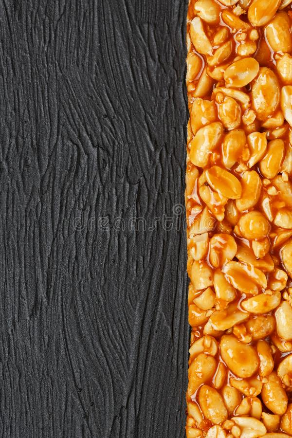 A large golden tile of peanuts, a bar in a sweet molasses on a black texture background. Kozinaki useful and tasty sweets of the stock image
