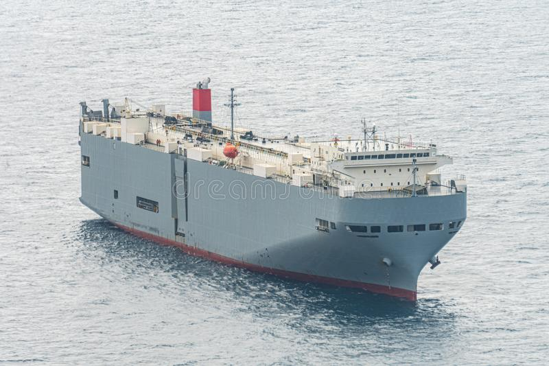 Large gray roll-on/roll-off RORO or ro-ro ships or oceangoing vehicle carrier ship anchor in the open sea. Roro ship designed to carry wheeled cargo such as royalty free stock photos
