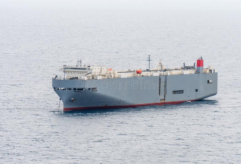 Large gray roll-on/roll-off RORO or ro-ro ships or oceangoing vehicle carrier ship anchor in the open sea. royalty free stock photography