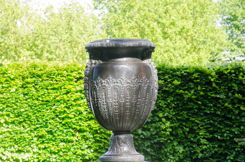 Large Greek style vase in formal garden with hedge. To rear royalty free stock images