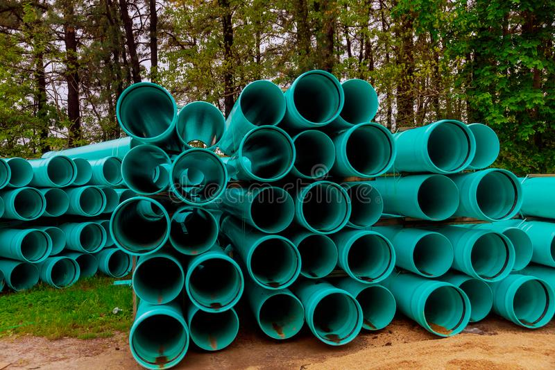 Large green industrial PVC sewer pipes road construction with barricades royalty free stock photography