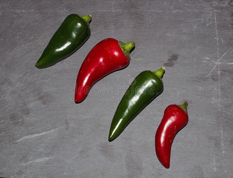 Large Green & Red Chili`s On A Slate Background. Large Green & Red Chilis On A Slate Background Tinted Green royalty free stock photography
