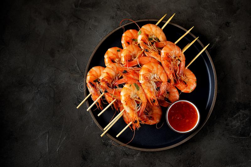 Large grilled prawns on wooden skewers. Shrimp kebabs. royalty free stock images