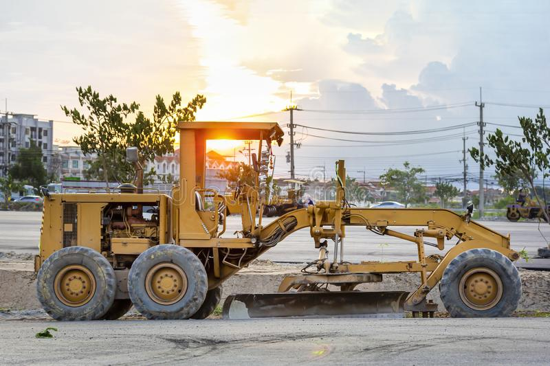 Large ground leveling machine or grader for road or street highway making park at work place with sunset at evening royalty free stock photo