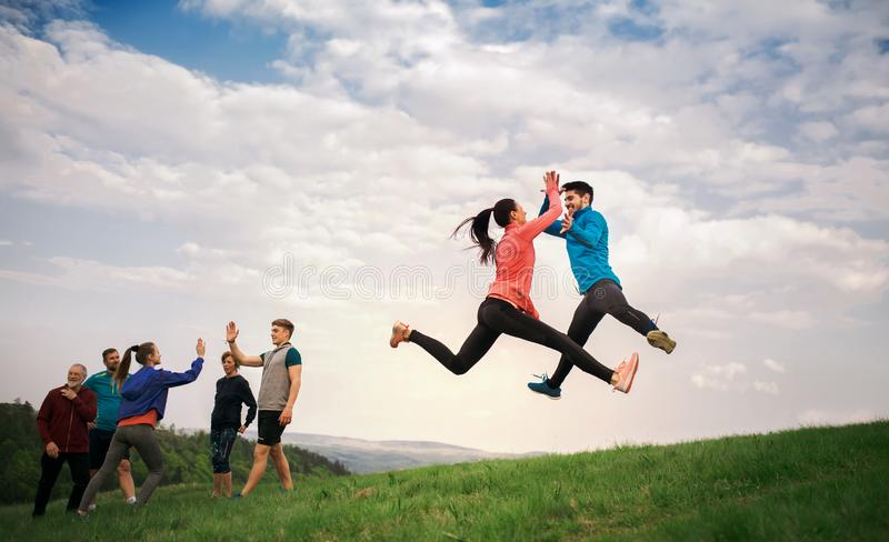 Large group of fit and active people jumping after doing exercise in nature. royalty free stock image