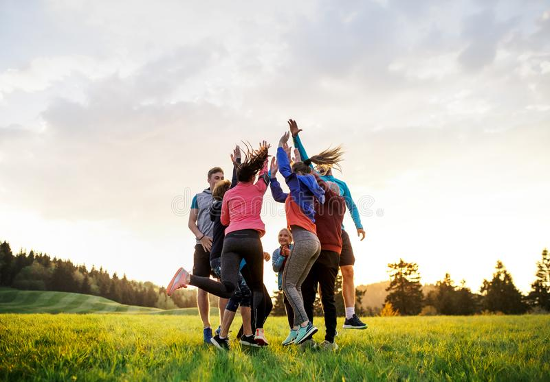 Large group of fit and active people jumping after doing exercise in nature. stock photo