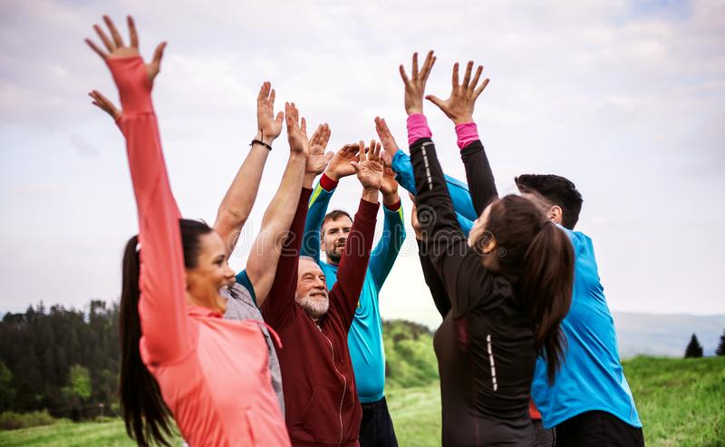 Large group of fit and active people resting after doing exercise in nature. royalty free stock photography