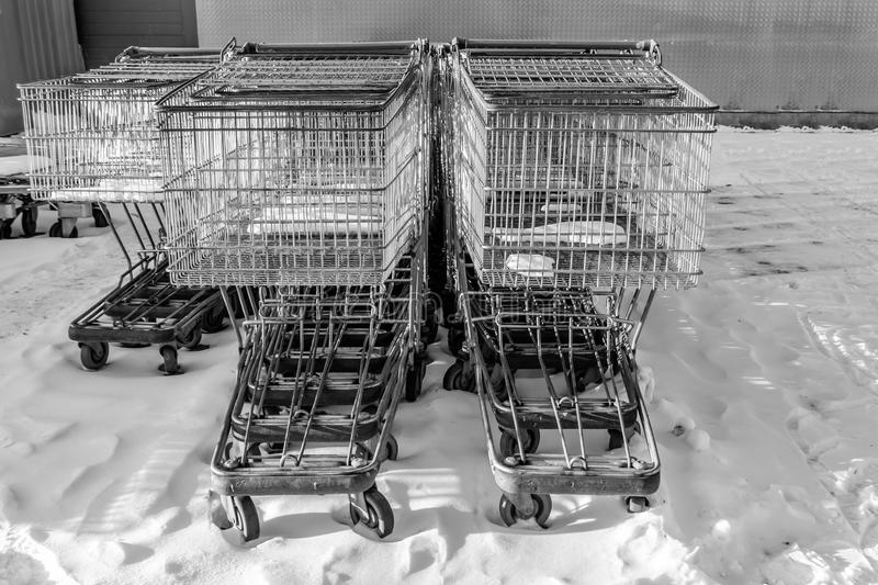 A large group of gray metal shopping storage baskets outside in the snow in winter by the supermarket royalty free stock image
