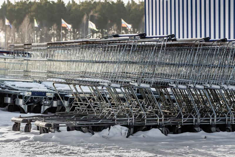 A large group of gray metal shopping storage baskets outside in the snow in winter by the supermarket stock image
