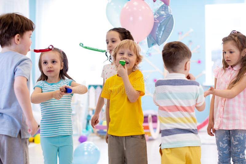 Large group of kids age 3 to 5 inside on a birthday party blowing noisemakers horns and twisted whistles royalty free stock photography