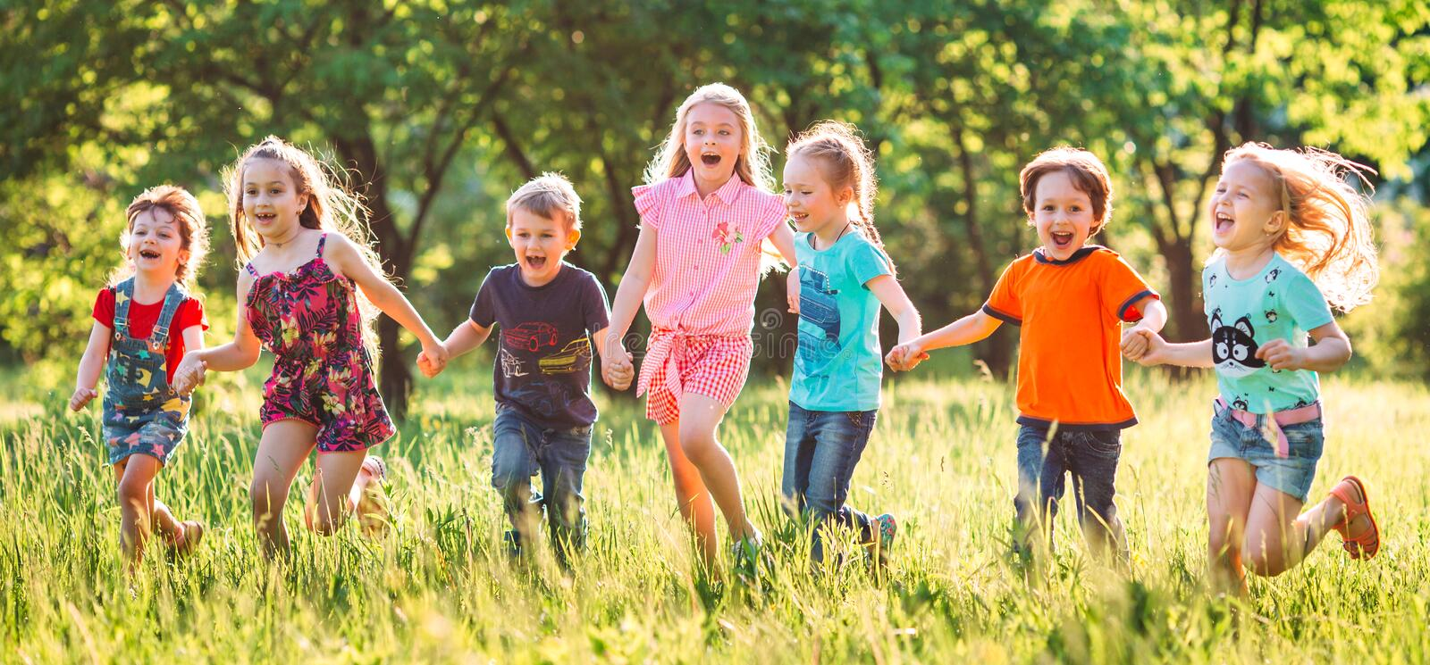 Large group of kids, friends boys and girls running in the park on sunny summer day in casual clothes . royalty free stock image