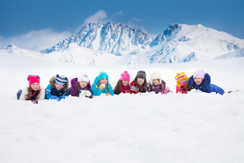 Large group of kids laying in snow royalty free stock photography