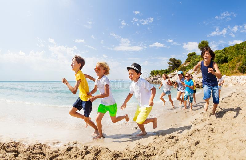 Large group of kids run on a beach along the sea royalty free stock photos