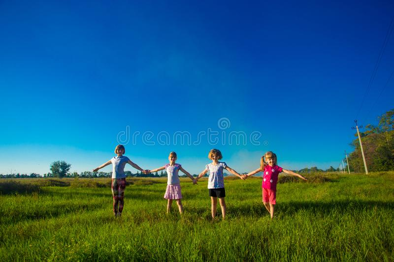 Large group of kids running in summer field royalty free stock photo