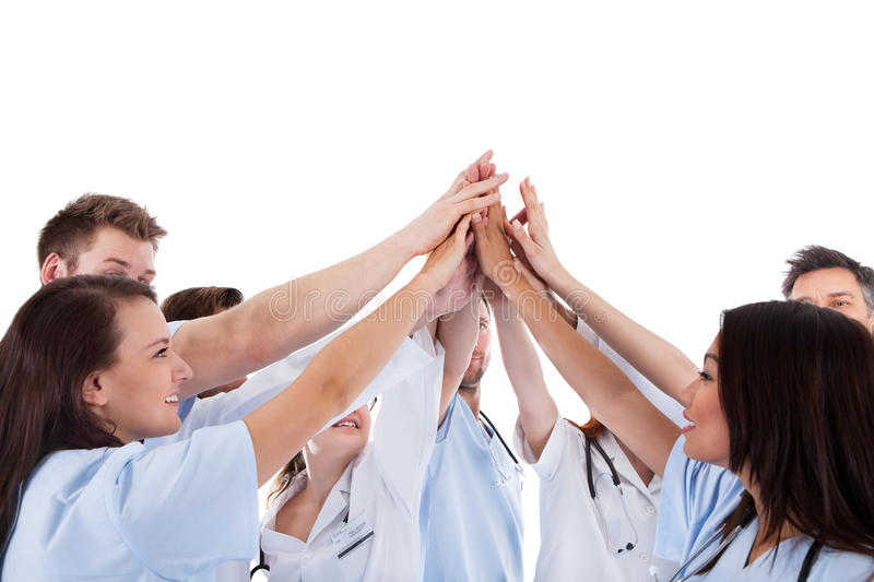 Large group of motivated doctors and nurses. Standing in a circle giving a high fives gesture with their hands meeting in the centre conceptual of teamwork royalty free stock photos