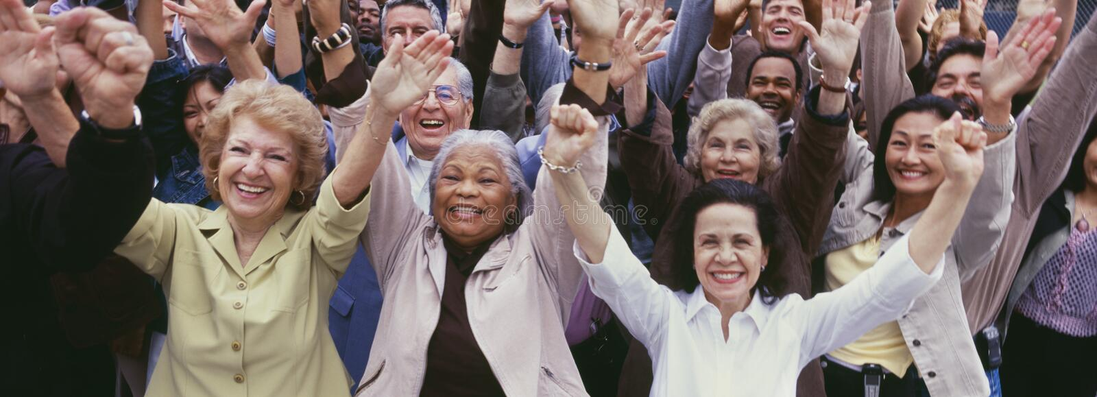 Large group of multi-ethnic people cheering with arms raised royalty free stock images