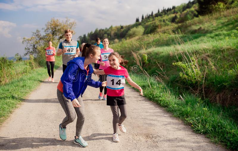 Large group of multi generation people running a race competition in nature. A large group of active multi generation people running a race competition in stock photography